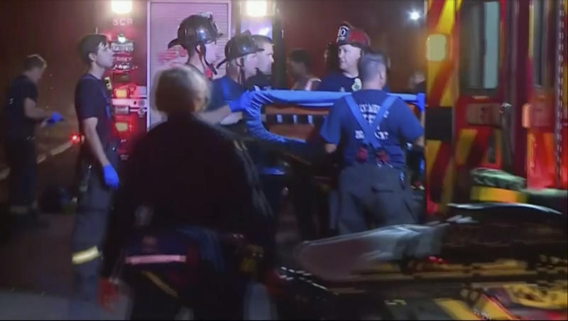 In this image from video, an emergency crew carries stretchers for injured persons after a light rail train was derailed in Sacramento, Calif., Thursday night, Aug. 22, 2019. Authorities say more than two dozen people have been injured in the light rail train derailment in Northern California. (KOVR via AP)