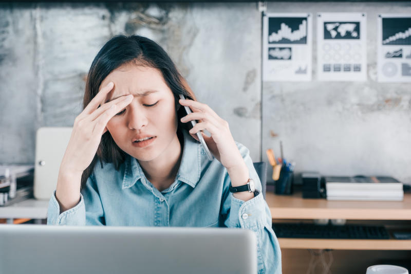 Stressed woman covers her face with hand and feels upset while talking on mobile phone in front of laptop computer at office.