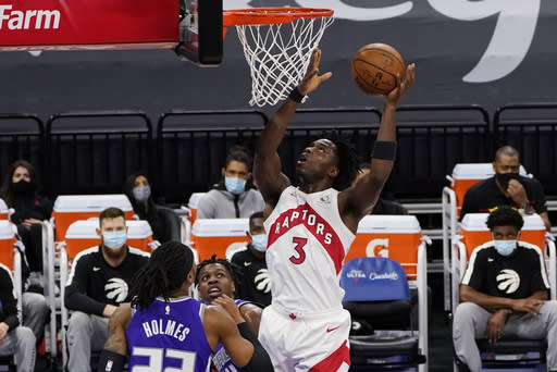 Toronto Raptors forward OG Anunoby goes to the basket over Sacramento Kings' Richaun Holmes, left, and Buddy Hield, center, during the first quarter of an NBA basketball game in Sacramento, Calif., Friday, Jan. 8, 2021. (AP Photo/Rich Pedroncelli)