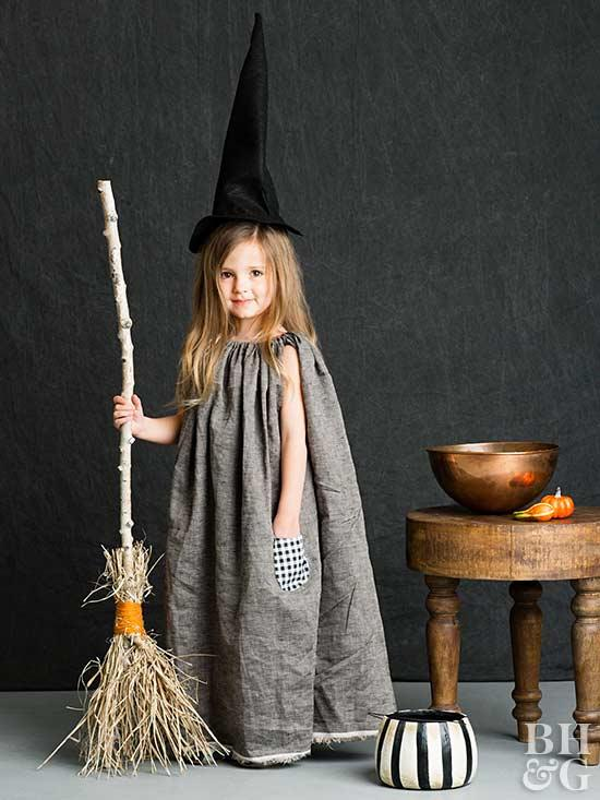 little girl dressed in a homemade halloween costume of a gray dress and black witch hat and witch broom