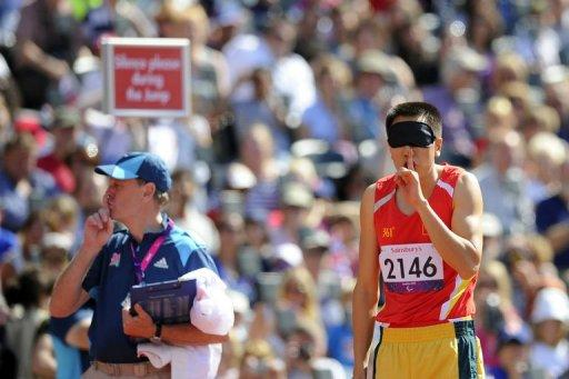 China's Li Duan signals for silence before the men's long jump F11 final