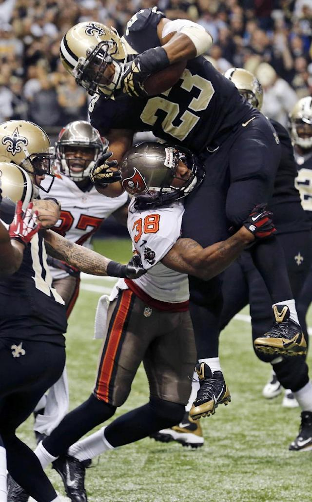 New Orleans Saints running back Pierre Thomas (23) leaps for a touchdown as Tampa Bay Buccaneers free safety Dashon Goldson (38) tries to keep him out of the end zone in the second half of an NFL football game, Sunday, Dec. 29, 2013, in New Orleans. (AP Photo/Bill Haber)