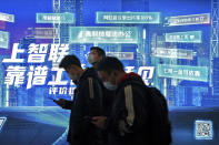 Commuters wearing face masks to help curb the spread of the coronavirus browse their smartphones as they walk by a mobile phone app advertisement at a subway station in Beijing Tuesday, March 2, 2021. Chinese leaders are shifting focus from the coronavirus back to long-term goals of making China a technology leader at this year's highest-profile political event, the meeting of its ceremonial legislature, amid tension with Washington and Europe over trade, Hong Kong and human rights. (AP Photo/Andy Wong)