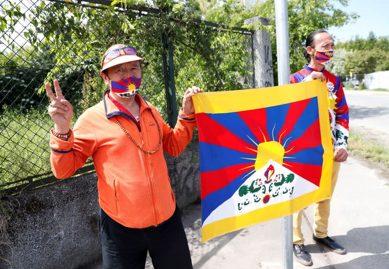 Activists hold a Tibetan flag next to a street sign in a street renamed 'Martyrs of Uyghur' in Budapest
