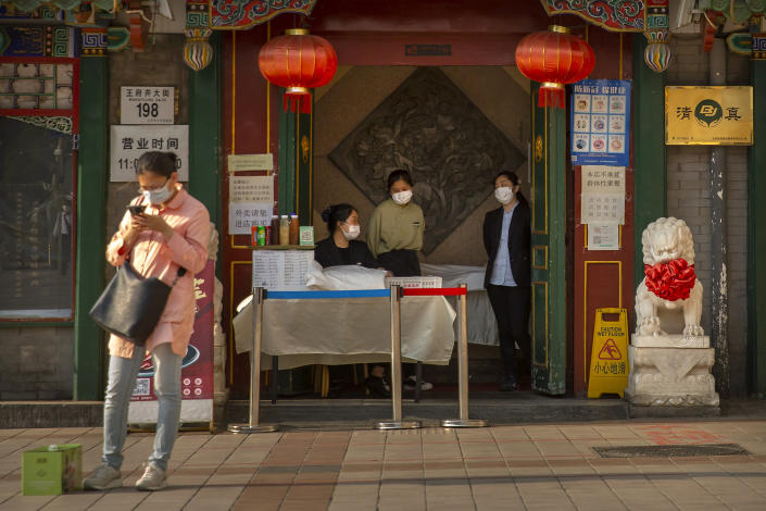 Clerks wear face masks to prevent the spread of the new coronavirus as they wait for customers at the entrance to a restaurant in Beijing, Tuesday, April 28, 2020. The Chinese city of Wuhan, which was the original epicenter of the pandemic, again reported no new coronavirus cases or deaths Tuesday and its hospitals remained empty of virus patients for a second straight day. (AP Photo/Mark Schiefelbein)