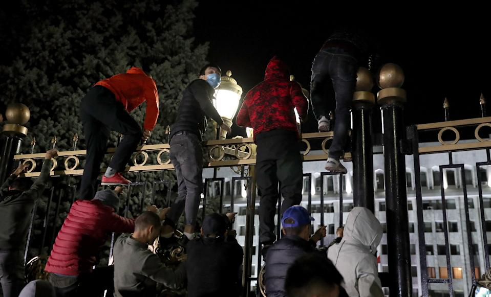 Opposition protesters storm the gates of the parliamentary building, known as the 'White House', in Bishkek (EPA)