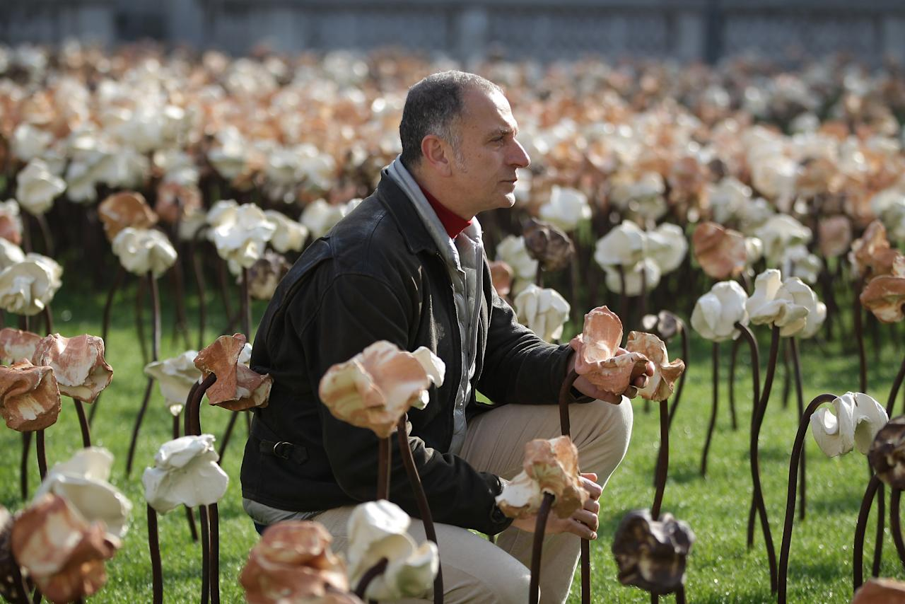 LONDON, ENGLAND - MARCH 15:  London based Chilean artist Fernando Casasempere poses with his 'Out of Sync' art installation on a grass meadow at Somerset House on March 15, 2012 in London, England. The artist hand crafted the 10,000 clay flowers that dominate the Edmond J. Safra Fountain Court. The installation is open to the public at Somerset House from March 16th to April 27th 2012.  (Photo by Peter Macdiarmid/Getty Images for Somerset House Trust)