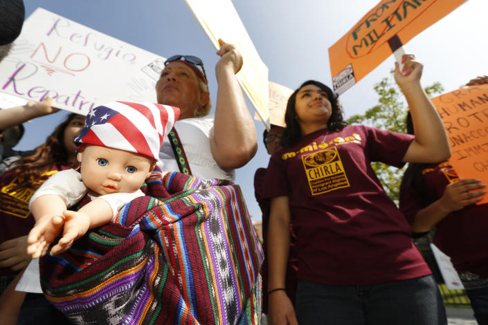 FILE - In this July 3, 2014, file photo, immigration activists Amarily Ortiz, left, and Mayra Sixtos, demand the Mexican government to take more measures to protect and respect the rights of unaccompanied minors and families crossing Mexico's territory during a protest outside the Mexican Consulate in Los Angeles. The U.S. federal government may house unaccompanied migrant children on a California Army National Guard base in central California, officials said. The Pentagon on Friday, April 2, 2021, approved the use of Camp Roberts to temporarily house children traveling alone, according to a defense official. (AP Photo/Damian Dovarganes, File)