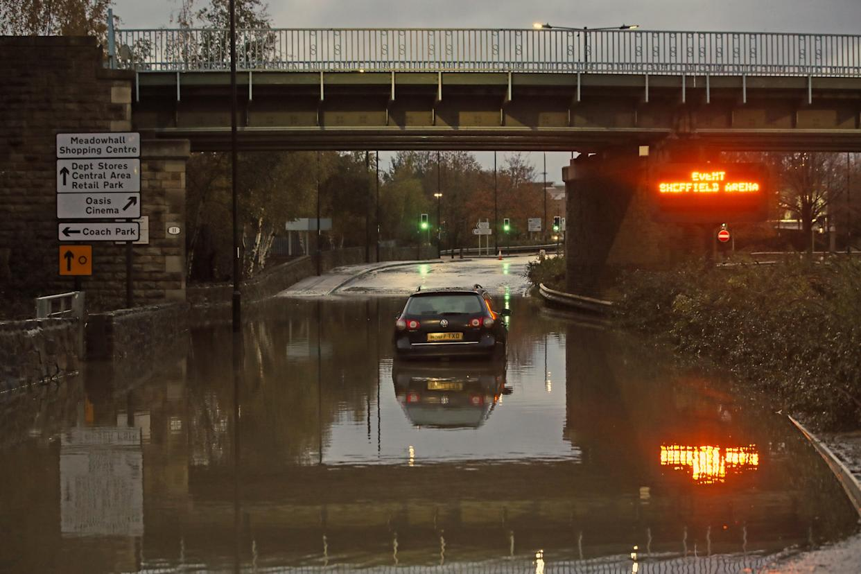 A car sits in floodwater near Meadowhall shopping centre in Sheffield where dozens were forced to stay overnight after flooding caused local roads to become gridlocked. (PA/Getty)