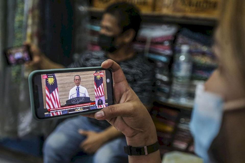 A store keeper at Jalan Tuanku Abdul Rahman watching the live telecast of Prime Minister Tan Sri Muhyiddin Yassin announcing the Pemerkasa programme, March 17, 2021. ― Picture by Hari Anggara