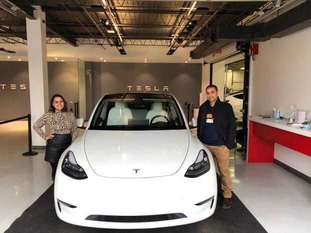 Chandresh Patel and his wife Sneha pose with their new Tesla in the showroom.
