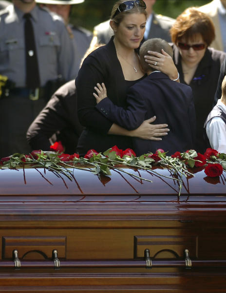 "FILE- In this Sept 18, 2014, file photo, Tiffany Dickson embraces her son Bryon III, in front of the casket of her husband Pennsylvania State Trooper Cpl. Bryon Dickson at the Dunmore Cemetery in Dunmore, Pa. ""I don't have a break. I'm just really tired,"" Tiffany Dickson told jurors Thursday, April 20, 2017, at the trial of her husband's killer. ""He was my break and he was a really good teammate. I'm just angry I can't grow old with him now."" (Butch Comegys/The Times & Tribune via AP, File)"