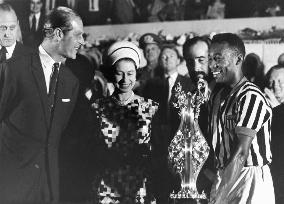 FILE - In this Nov. 10, 1968 file photo, Britain's Queen Elizabeth II with Prince Philip present a cup to soccer player Pele, right, at a stadium in Rio de Janeiro, Brazil, during a state tour of South America. Buckingham Palace officials say Prince Philip, the husband of Queen Elizabeth II, has died, it was announced on Friday, April 9, 2021. He was 99. Philip spent a month in hospital earlier this year before being released on March 16 to return to Windsor Castle. Philip, also known as the Duke of Edinburgh, married Elizabeth in 1947 and was the longest-serving consort in British history. (AP Photo/File)