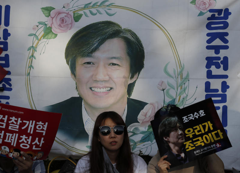 "A picture of South Korea's Justice Minister, Cho Kuk is seen before a rally supportin Cho in front of Seoul Central District Prosecutors' Office in Seoul, South Korea, Saturday, Oct. 12, 2019. The letters read ""Reform the Prosecution"" and ""Protect Cho Kuk"".  Tens of thousands of government supporters have gathered in South Korea's capital for the fourth-straight weekend to show their support for President Moon Jae-in's controversial justice minister who's enmeshed in explosive political scandal that rocked and polarized the nation.(AP Photo/Lee Jin-man)"