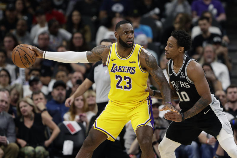 Los Angeles Lakers forward LeBron James (23) and San Antonio Spurs guard DeMar DeRozan (10) during the second half of an NBA basketball game, in San Antonio, Monday, Nov. 25, 2019. (AP Photo/Eric Gay)