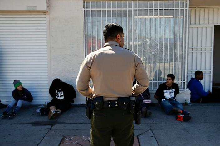 A Los Angeles County Sheriff's deputy keeps watch on a group of people apprehended at an illegal marijuana dispensary in Compton, Calif.