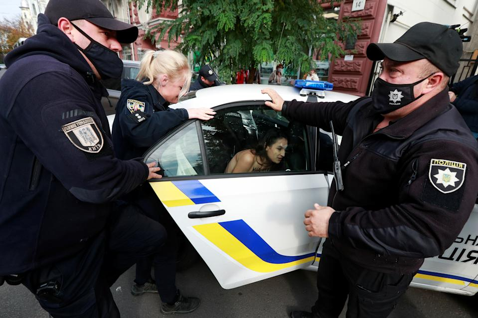 Police officers detain a Femen activist as she stages an action in support of Polish demonstrators protesting against imposing further restrictions on abortion law, in front of the Polish embassy in Kyiv, Ukraine October 26, 2020. REUTERS/Valentyn Ogirenko