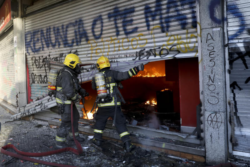ADDS FIRE WAS STARTED BY PROTESTERS - Firefighters force open the bottom floor of a small shopping center that was set fire by anti-government protesters in Santiago, Chile, Monday, Oct. 28, 2019. Fresh protests and attacks on businesses erupted in Chile Monday despite President Sebastián Piñera's replacement of eight important Cabinet ministers with more centrist figures, and his attempts to assure the country that he had heard calls for greater equality and improved social services.(AP Photo/Rodrigo Abd)