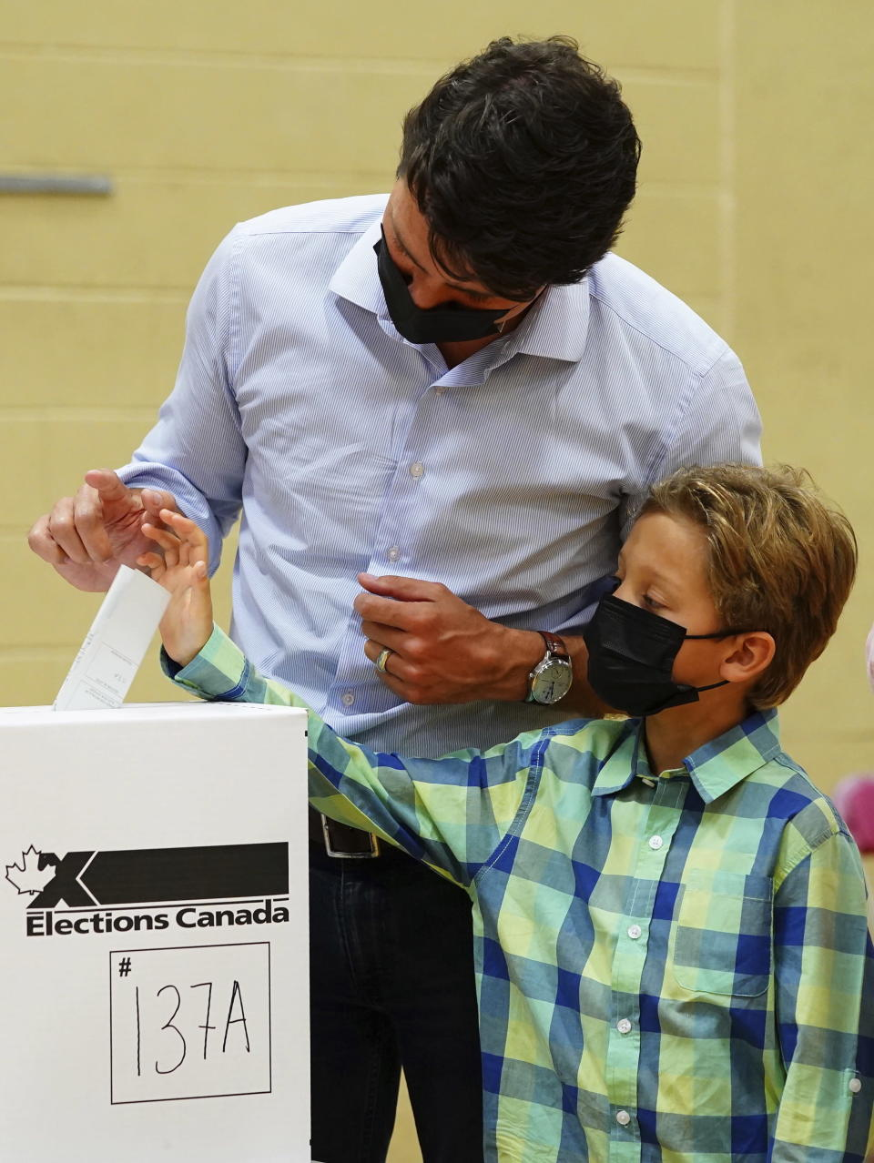 Liberal leader Justin Trudeau casts his ballot in the 44th general federal election as he's joined by his son Hadrien in Montreal on Monday, Sept. 20, 2021. (Sean Kilpatrick/The Canadian Press via AP)