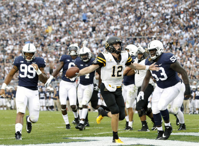 FILE - In this Sept. 1, 2018, file photo, Appalachian State quarterback Zac Thomas (12) runs in for a touchdown against Penn State during the second half of an NCAA college football game in State College, Pa. Appalachian State returns nine all-Sun Belt players from last season, including the 2018 offensive player of the year in quarterback Zac Thomas. (AP Photo/Chris Knight, File)
