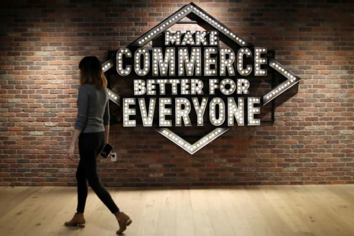 FILE PHOTO: An employee walks past a sign at Shopify's headquarters in Ottawa