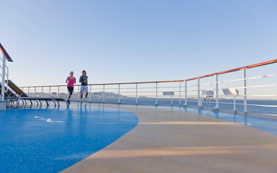 Couple jogging on deck of cruise ship - Getty