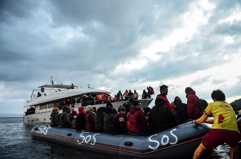 Migrants arrive on a rubber dinghy on the Greek island of Lesbos after crossing the Aegean Sea from Turkey on November 21, 2015