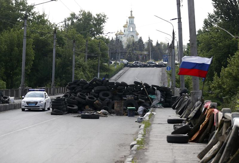 "A car passes by the barricades with a Russian national flag on a road leading into Slovyansk, eastern Ukraine, Tuesday, May 13, 2014. Pro-Russian insurgents, who have seized government buildings and clashed with government forces during the past month, held Sunday's referendum, which Ukraine's acting president called a ""sham"" and Western governments said violated international law. (AP Photo/Darko Vojinovic)"