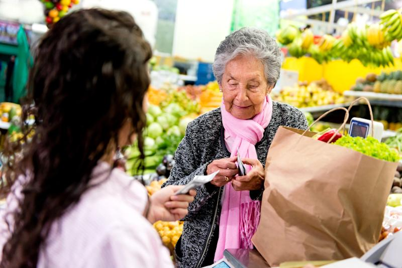 Woman customer paying at the supermarket after buying groceries