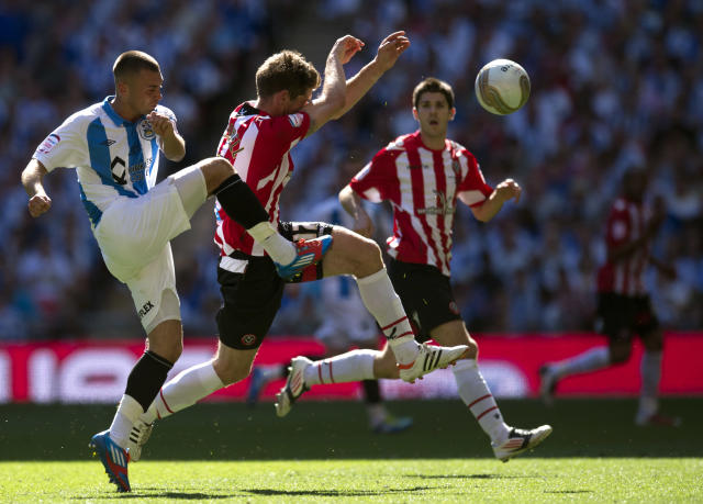 Huddersfield Town's Jack Hunt (L) clears the ball in front of Sheffield United's Richard Cresswell (C) during the League 1 Play-Off Final football match at Wembley Stadium in London on May 26, 2012. Huddersfield won the game 8-7 on penalties to win promotion to the Championship next season. AFP PHOTO / ADRIAN DENNISADRIAN DENNIS/AFP/GettyImages