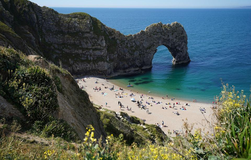 A woman died after falling from Durdle Door in front of beachgoers (PA)