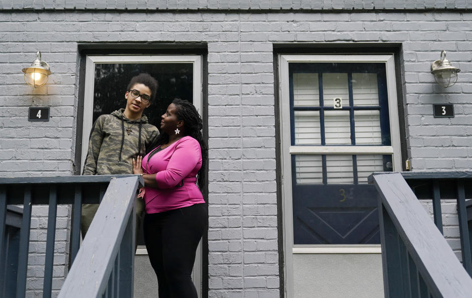 """Dylyn Price, right, and her son Devone, 14, both of Athens, Ga., stand outside of their rented townhome on Tuesday, June 22, 2021, in Athens, Ga. A rental crisis spurred by the pandemic prompted many states to make bold promises to help renters, but most failed to deliver on them after Congress passed the sweeping CARES Act in March 2020. Price said she got about $5,800 in rental assistance but that may not prevent her from losing her home. """"It's a very nauseating and uncomfortable situation to be in,"""" Price said. (AP Photo/Brynn Anderson)"""
