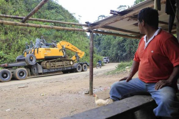 Former gold miner Carlos Guallas watches as police prepare to evict illegal miners in the Guanguiza minery area of Paquisha September 16, 2010.