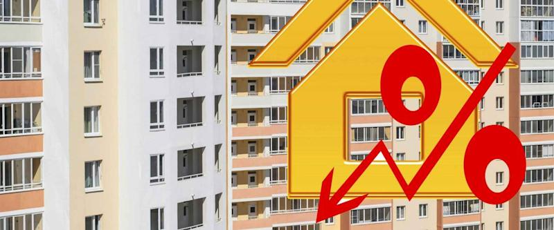 Red percent sign on the background of the houses. The concept of price changes in the real estate market.