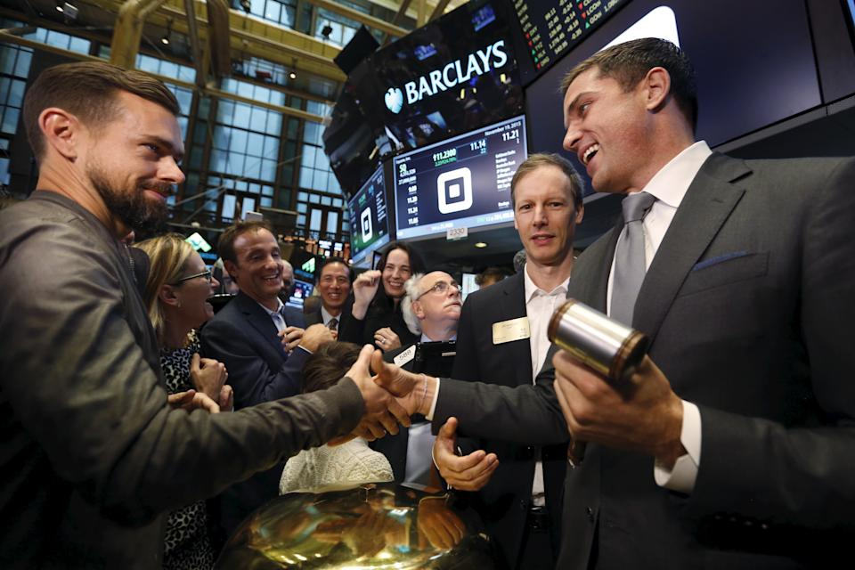 Jack Dorsey (L), CEO of Square and CEO of Twitter, is congratulated by Jim McKelvey, co-founder of Square, (2nd R) and NYSE President Tom Farley (R) after the IPO of Square Inc., in New York November 19, 2015. Square Inc priced shares at $9 for its initial public offering, about 25 percent less than it had hoped, as it struggled to win over investors skeptical about its business and valuation before trading begins on Thursday.  REUTERS/Lucas Jackson