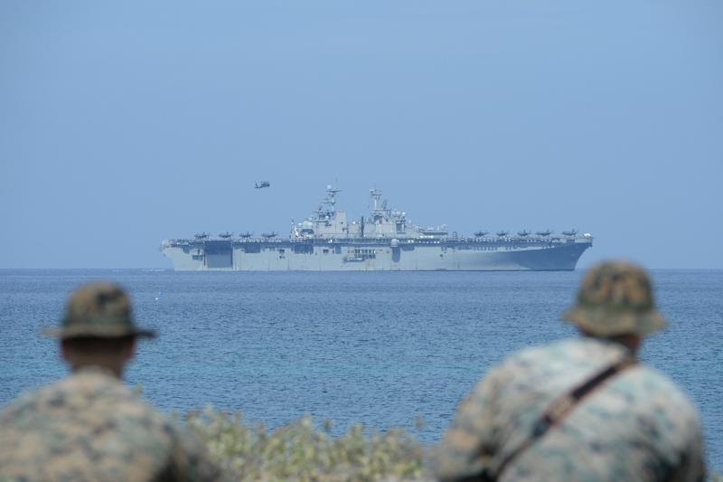 US Marines watch the US navy multipurpose amphibious assault ship 'USS Wasp' with F-35 lightning fighter jets on the deck during the annual joint US-Philippines military exercise on April 11, 2019 (AFP Photo/TED ALJIBE)