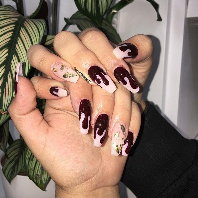 """<p>Thick, maroon blood is offset by gold foil on the ring finger on these cool, coffin nails.</p><p><a href=""""https://www.instagram.com/p/B3eYwmKH3IU/"""" rel=""""nofollow noopener"""" target=""""_blank"""" data-ylk=""""slk:See the original post on Instagram"""" class=""""link rapid-noclick-resp"""">See the original post on Instagram</a></p>"""