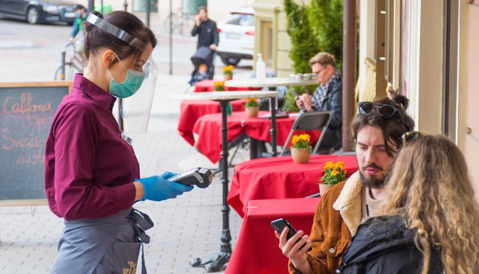 Waitress with a mask and clients at an outdoor bar, café or restaurant, reopen after quarantine restrictions.