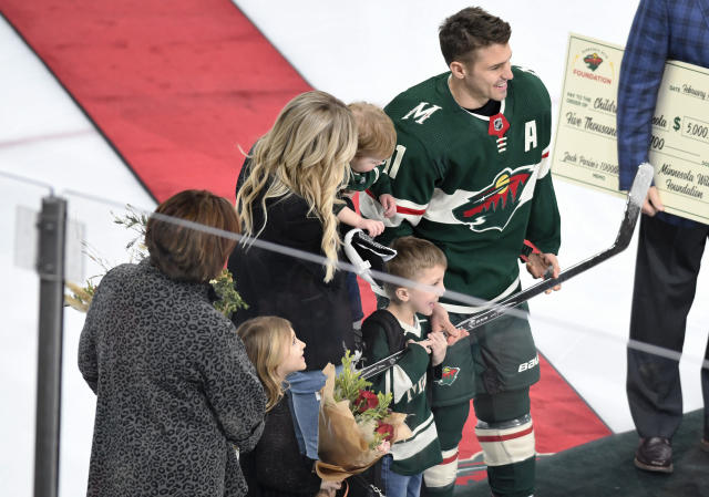 Minnesota Wild's Zach Parise, right, poses with his family and a silver stick emblematic of play in 1,000 career hockey game prior to the Wild's game against the San Jose Sharks in an NHL hockey game, Saturday, Feb. 15, 2020, in St. Paul, Minn. (AP Photo/Tom Olmscheid)