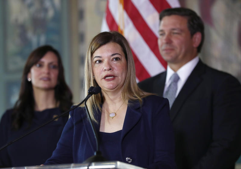 Barbara Lagoa, Governor Ron DeSantis' pick for the Florida Supreme Court, speaks after being introduced, Wednesday, Jan. 9, 2019, in Miami. At rear right is Gov. Ron DeSantis and at left lieutenant governor Jeanette Nunez. (AP Photo/Wilfredo Lee)
