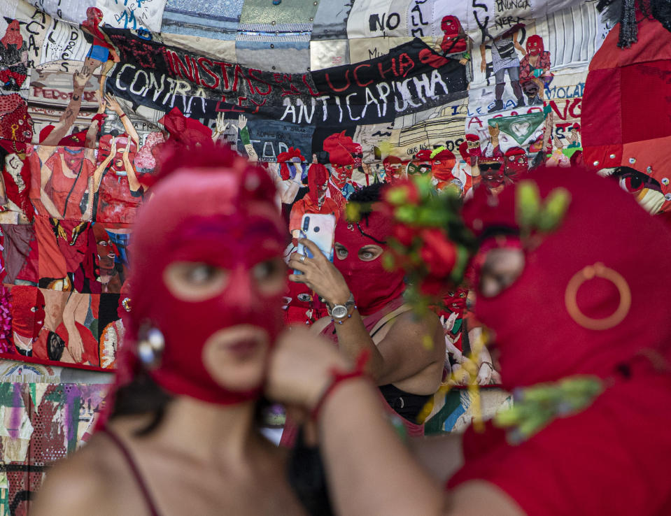 Women put on their masks while another takes a selfie prior to a march for International Women's Day in Santiago, Chile, on Monday, March 8, 2021. (AP Photo/Esteban Félix)