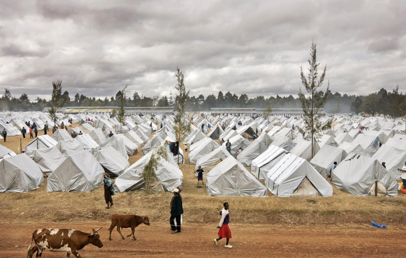 FILE - In this Saturday, Jan. 19, 2008 file photo, a sea of tents made out of plastic sheeting fills a camp for those displaced by post-election violence in the showground in Eldoret, Kenya. A Kenyan woman said Thursday, Sept. 19, 2013 that she fears for her life after her photo was circulated on social media and on blogs claiming she was the first witness - whose identity was hidden - to testify against Kenya's deputy president during his trial at the International Criminal Court. (AP Photo/Ben Curtis, File)