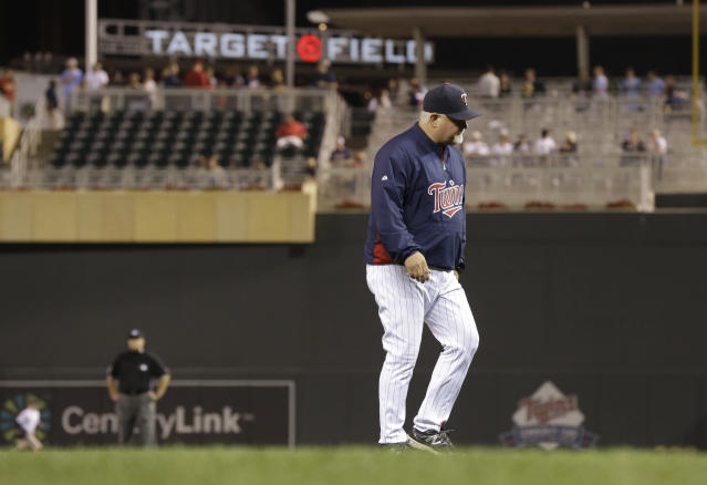 Minnesota Twins manager Ron Gardenhire returns to the dugout after a pitching change in the eighth inning of the Twins' baseball game against the Cleveland Indians, Thursday, Sept. 26, 2013, in Minneapolis. The Indians won 6-5. (AP Photo/Jim Mone)