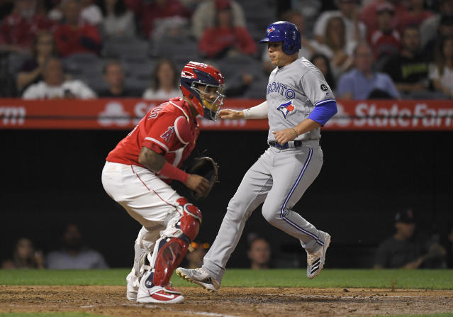 Toronto Blue Jays' Aledmys Diaz, right, scores on a double by Devon Travis as Los Angeles Angels catcher Martin Maldonado stands at the plate during the seventh inning of a baseball game Friday, June 22, 2018, in Anaheim, Calif. The Angels won 2-1. (AP Photo/Mark J. Terrill)