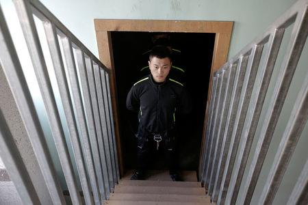 A trainee from Dewei Security waits to attend a daily training session at a training camp on the outskirts of Beijing