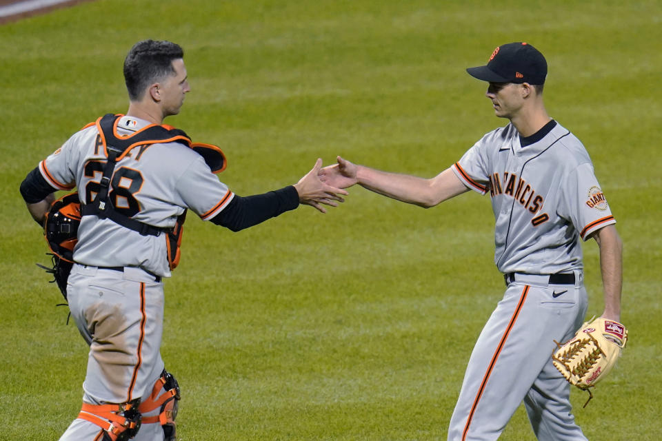 San Francisco Giants relief pitcher Tyler Rogers, right, shakes hands with catcher Buster Posey after the team's 3-1 win over the Pittsburgh Pirates in a baseball game in Pittsburgh, Thursday, May 13, 2021. (AP Photo/Gene J. Puskar)