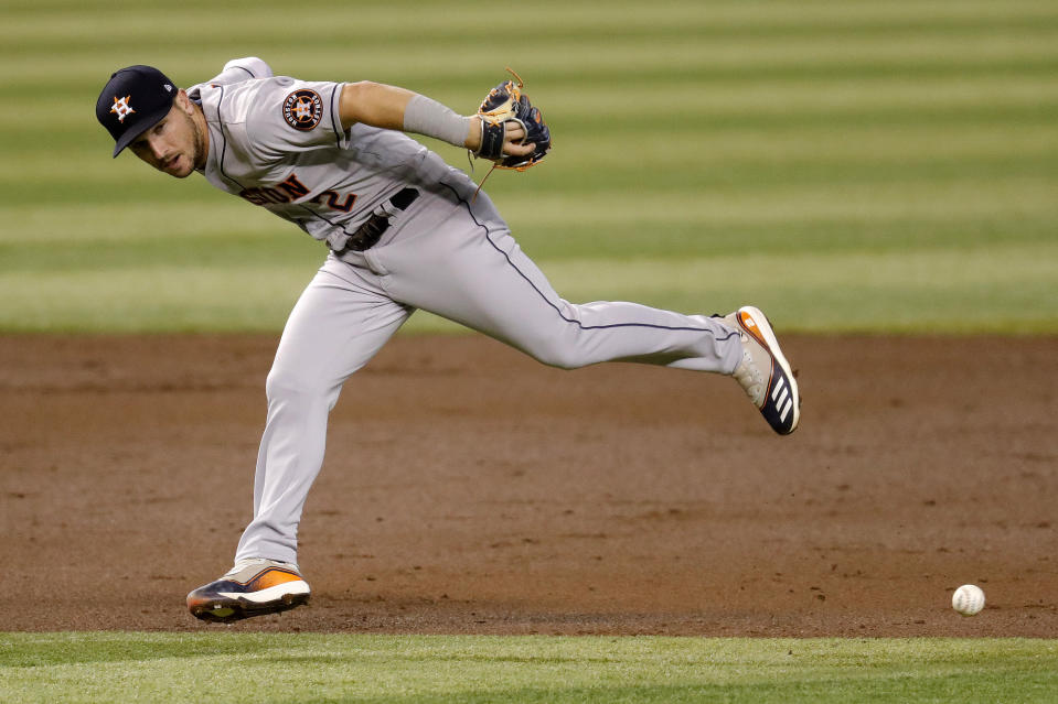 Houston Astros' Alex Bregman (2) can't get a glove on base hit by Arizona Diamondbacks David Peralta during the second inning of a baseball game Tuesday, Aug. 4, 2020, in Phoenix. (AP Photo/Matt York)