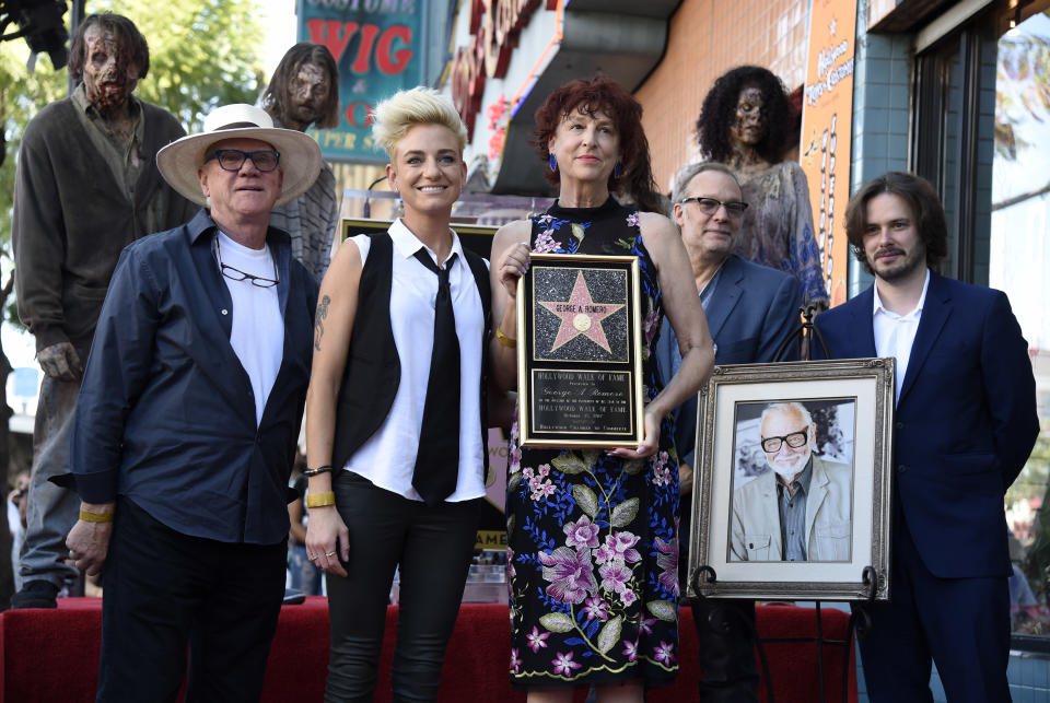 """Suzanne Desrocher, center, the widow of the late director George A. Romero, is joined by actor Malcolm McDowell, foreground from left, Romero's daughter Tina, special effects/makeup artist Greg Nicotero and director Edgar Wright during a ceremony awarding Romero with a star on the Hollywood Walk of Fame on Wednesday, Oct. 25, 2017, in Los Angeles. Romero, the writer/director of the 1968 zombie film """"Night of the Living Dead,"""" died on July 16. (Photo by Chris Pizzello/Invision/AP)"""