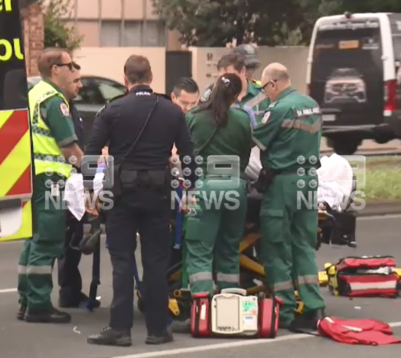 paramedics are seen tending to the police officer at the scene.