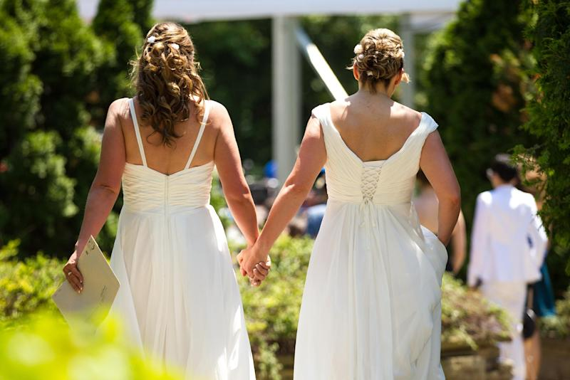Cheryl Taylor and Jennifer Smith hold hands as they arrive for the Grand Pride Wedding, a mass gay wedding at Casa Loma in Toronto, Canada, on June 26, 2014 (AFP Photo/Geoff Robins)